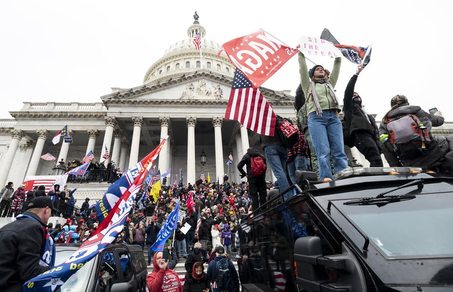 Trump supporters waving Trump and Confederate flags on the steps of the Capitol Building