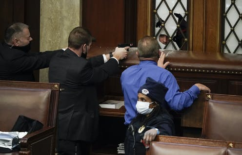 Security guards pull their guns on a protester who is outside of the House chamber