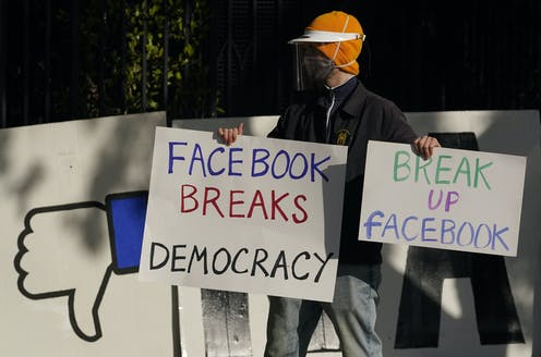 A man wearing a mask carries anti-Facebook signs calling for the tech giant to be broken up.