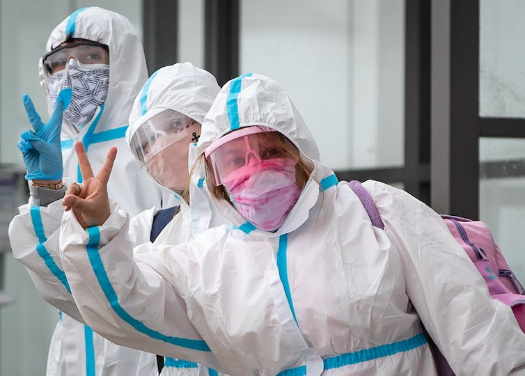 Three travellers in masks, face shields and white haz-mat suits give the peace sign to a photographer.