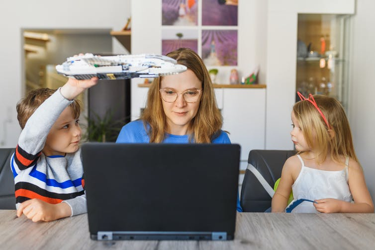 woman trying to concentrate on work while being distracted by two children