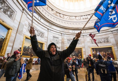 A pro-Trump rioter waving flags and shouting inside the US Capitol building, surrounded by other protesters.