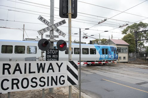 a train travels through a level crossing with the boom gates down