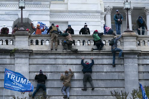 Protesters climbing a wall into Capitol building