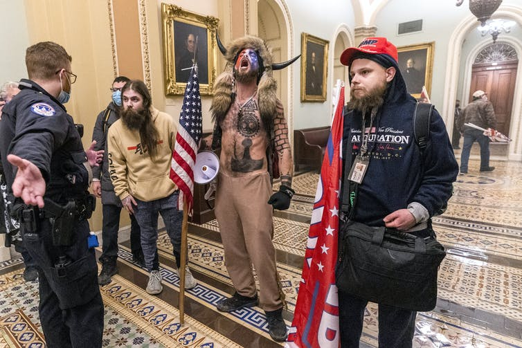 Several protesters, including a shirtless man wearing a fur hat with horns, confront a security guard at the U.S. Capitol.