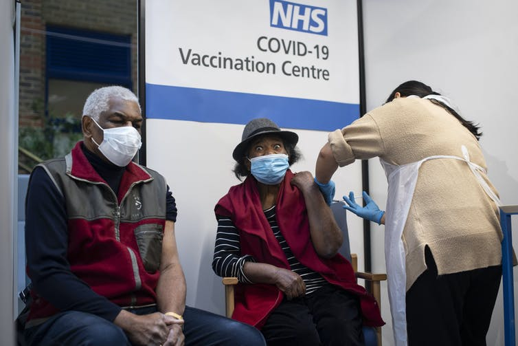 Patients receive COVID vaccines at a UK clinic
