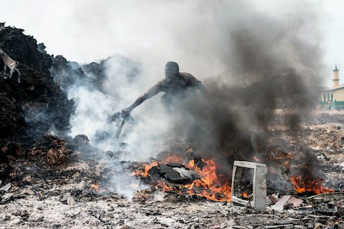 A man sorts burning electronic waste in a dumpsite.