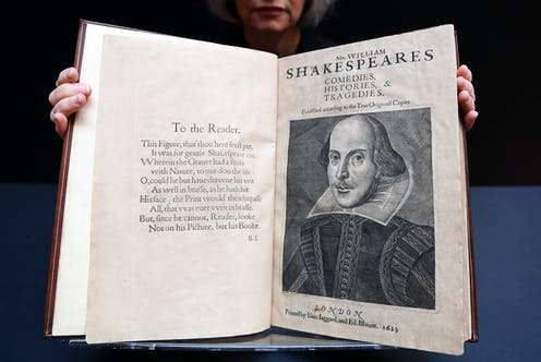 Person holding William Shakespeare's First Folio open towards the camera