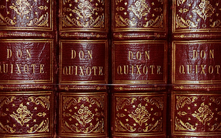 Red hard-bound editions of Miguel de Cervante's Don Quixote books in a row on a shelf