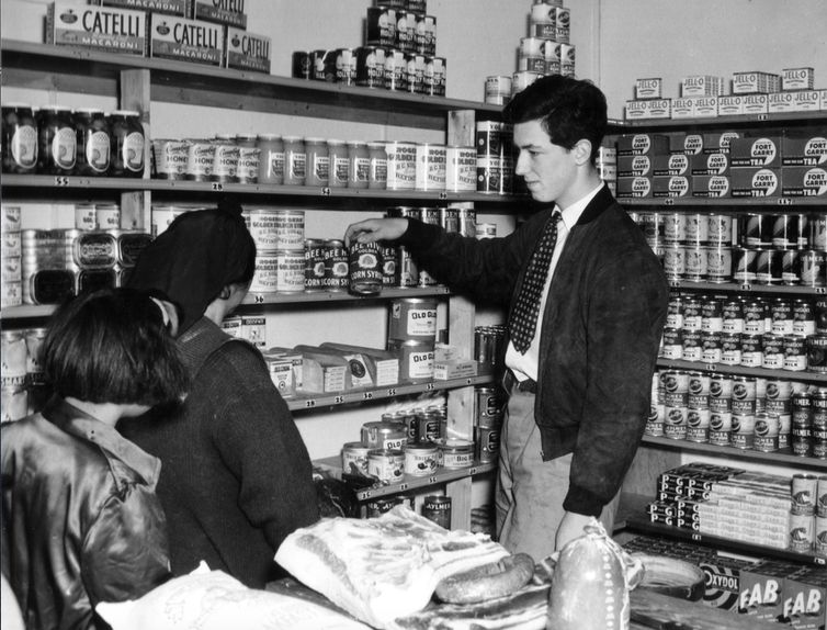 A young man in a shop with two female customers.