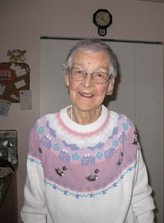 An elderly woman smiling into the camera.