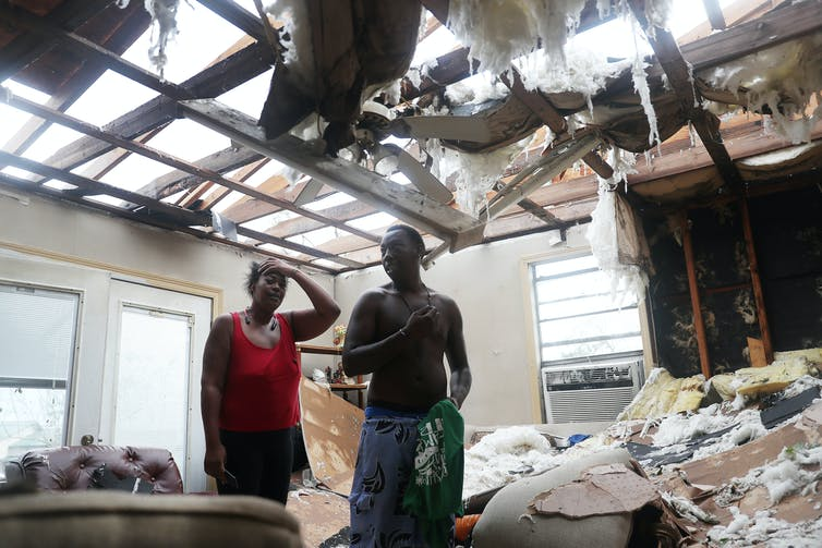 Latasha Myles and Howard Anderson stand in the living room where they were sitting when the roof blew off