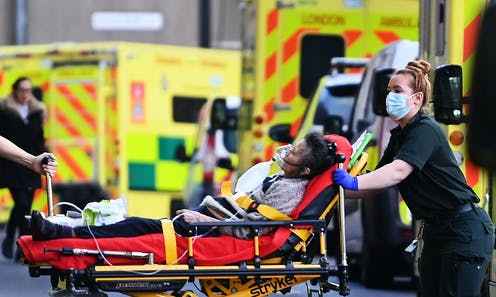 A paramedic transporting a patient on a stretcher from an ambulance into hospital.