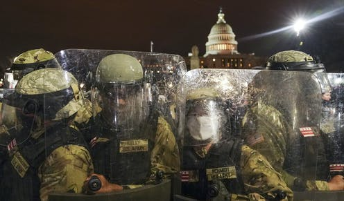 Police in riot gear stand outside the U.S. Capitol