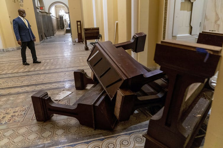 A senator looks at toppled furniture in a marble hallway.