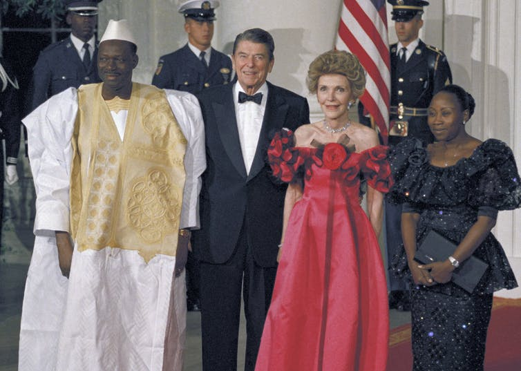 An African leader stands next to Ronald Reagan and their wives.