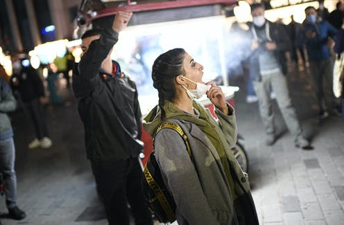 A woman pulls down her face mask to chant slogans