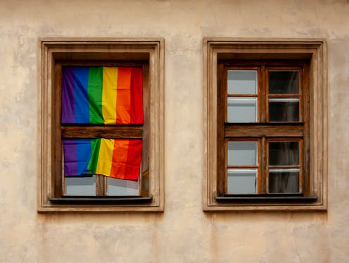 Two wooden frame windows are shown. The window on the left has a rainbow flag draped over it.