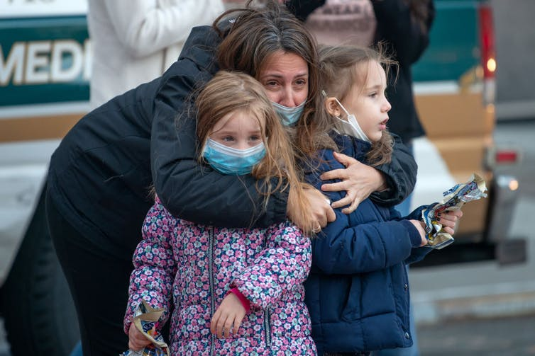 A women hugs two young girls.