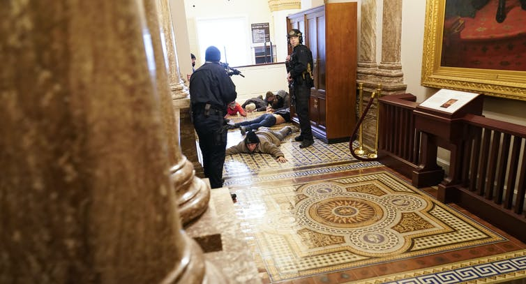 Police hold protesters at gunpoint as they lie on a marble floor.