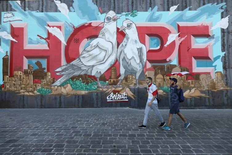 People walk past a wall mural of hope.