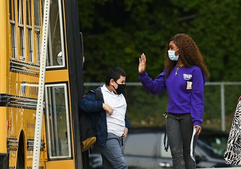 An adult in face mask greets a student getting off a bus.