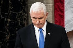 Pence looks down.