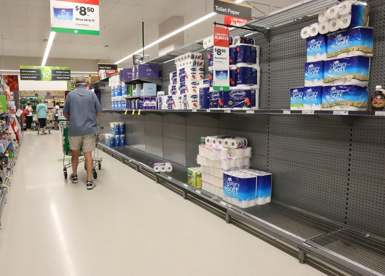 Man walks past half-empty supermarket shelves containing toilet roll