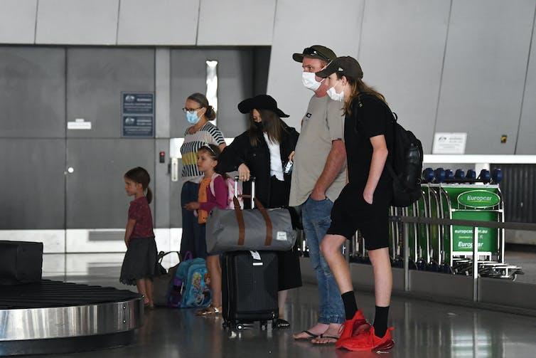 Family at baggage carousel wearing masks