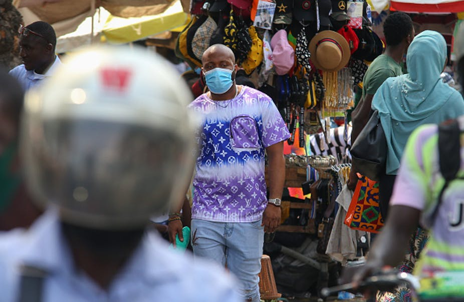 Man wearing mask, walking among other people with market stall in background