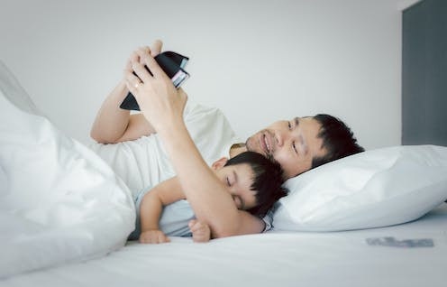 Unemployed stress asian man is hugging his baby on the bed and looking the wallet to find the money to pay for the expense and loan , concept of impact of covid 19 to personal financial problem.