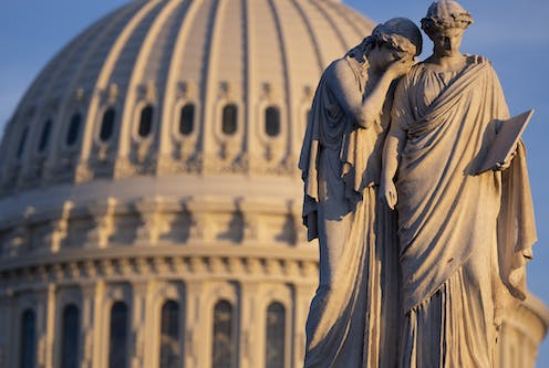 Classical statue of two figures against the backdrop of the US Capitol Building, Washington.