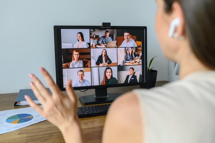 Woman video conferences with others on a screen