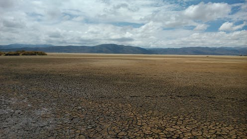 Dry lake bed with mountains in the distance.