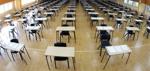 Empty exam hall with tables and chairs
