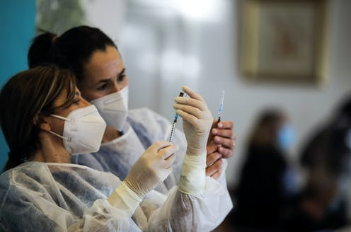 Healthcare workers prepare vaccines at a care home in Portugal