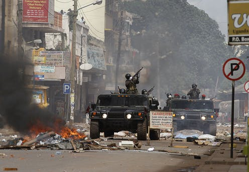 Soldiers point guns while riding military vehicles down a street where a pile of material is burning