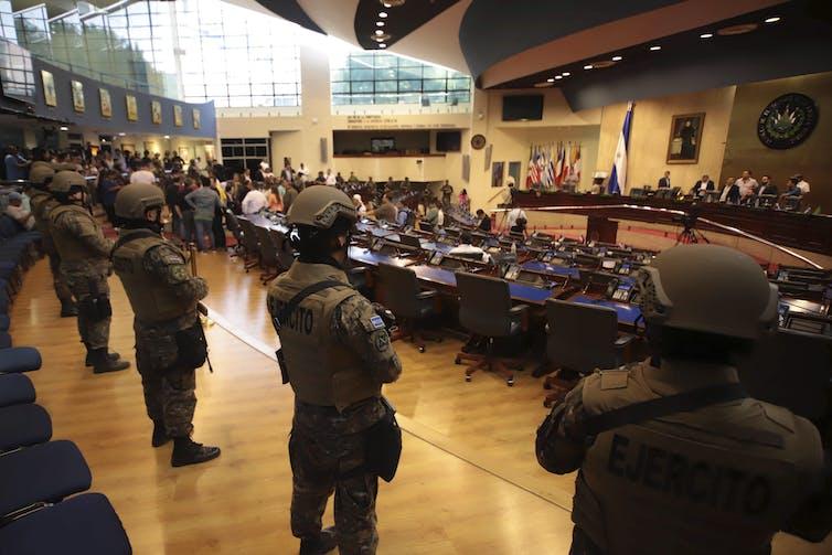 Armed soldiers stand in El Salvador Congress as lawmakers arrive.