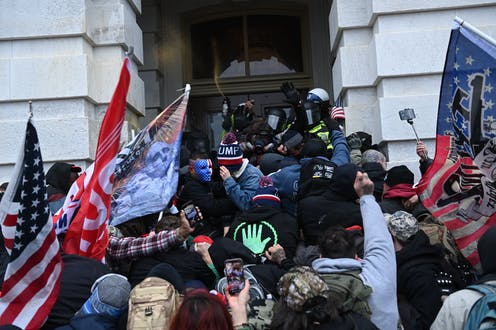 A crowd of people, some holding flags and some holding phones, press several police officers against a door