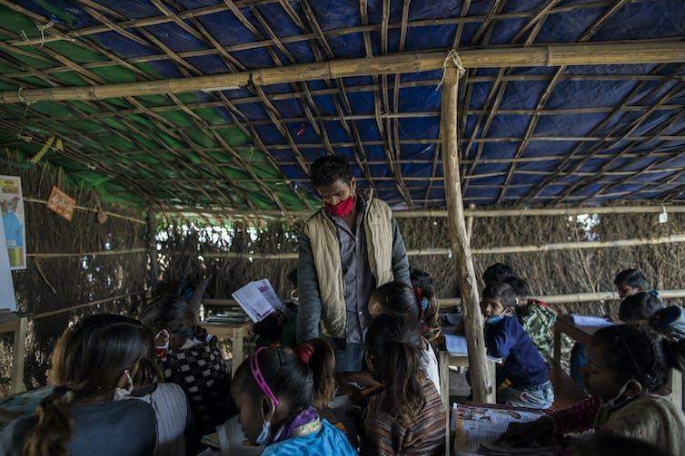Man in facemask supervises children under a makeshift hut