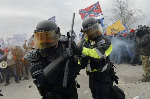 Two members of law enforcement surrounded by crowd, flags and smoke