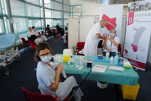 Des personnels médicaux vaccinent dans un centre dédié à la vaccination.