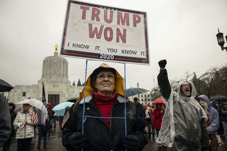 A woman at a protest holding a sign reading TRUMP WON I KNOW IT YOU KNOW IT