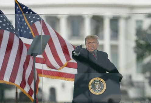 President Trump behind the podium points at the crowd with two American flags behind him
