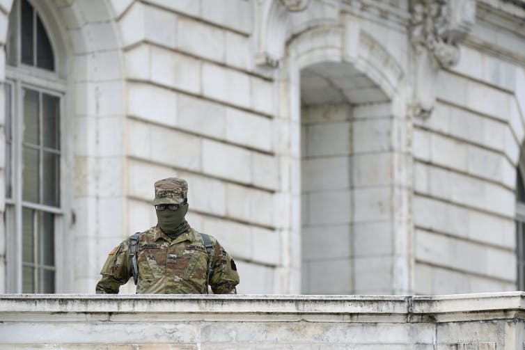 A member of the military stands guard outside Russell Senate Office Building on Capitol Hill