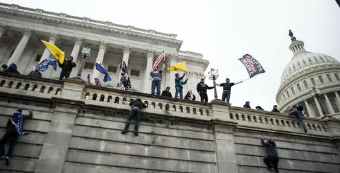 Supporters of U.S. President Donald Trump climb a wall  of the the U.S. Capitol