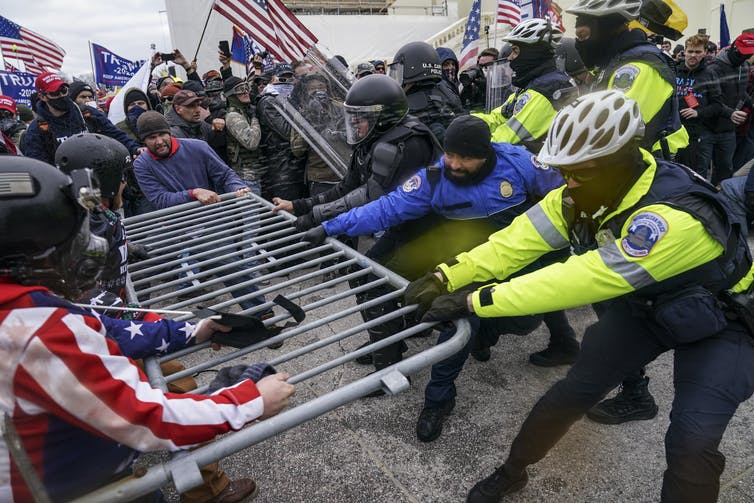 Police and protesters engage in a tug of war over a metallic barrier.