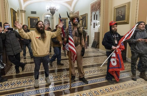 Three pro-Trump rioters, one wearing an employee ID badge around his neck, are seen outside the Senate Chamber inside the Capitol on Jan. 6.
