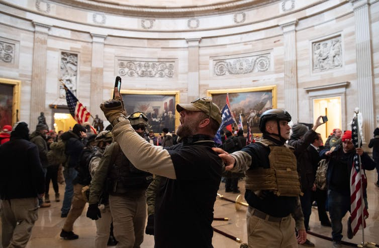 A throng of Trump supporters stand in the U.S. Capitol Rotunda on Jan. 6 as one snaps a picture.