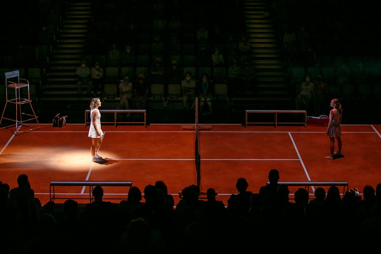 The audience on two sides of a red tennis court as a stage.